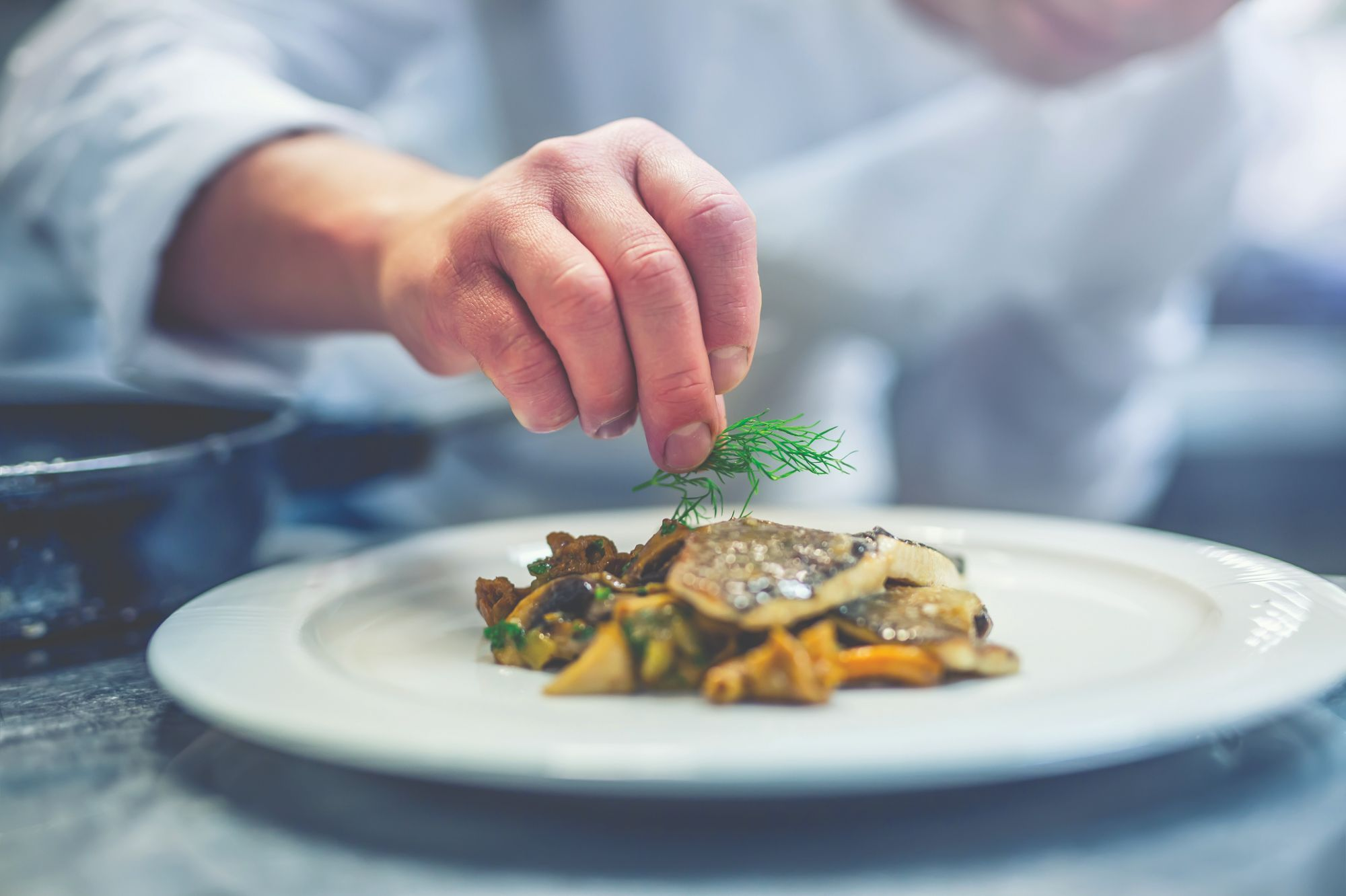 Chef garnishing gourmet meal in dining room at Charter Senior Living of Oak Openings